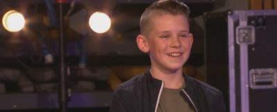 A boy with blonde hair smiles as he auditions for Taking the Next Step.