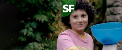 A young boy with curly hair holds a blue bowl, Tyler from The Dumping Ground.