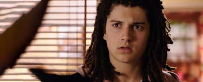 A young boy with dark dreadlocked hair looks confused in an office, Tyler from The Dumping Ground.