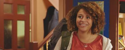 A young girl in a living room smiling, Charlie from The Dumping Ground.