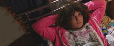 A boy lying on his bed with his hands behind his head, Tyler from The Dumping Ground.