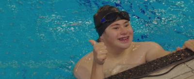 A boy swimming in a pool wearing a swimming cap and giving a thumbs up sign, Finn from The Dumping Ground.