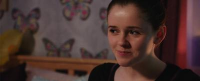 A girl sat in her bedroom looking happy, Chloe from The Dumping Ground.