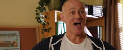 A man in an office looking surprised and happy, Mike from The Dumping Ground.