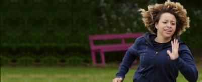 Charlie, a female character from The Dumping Ground. She is a young mixed race girl, with blonde curly hair. She is wearing a gery/black hoody and running.