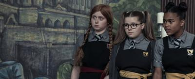 Three young girls in Cackle's Academy uniforms: Mildred, Maud and Enid are in a line. They are all looking into the distance shocked.