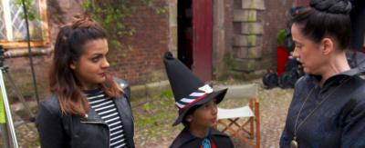 A young girl in a witches costume looking up as Miss Hardbroom from The Worst Witch.