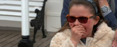 A young girl in a coat and sunglasses looking shocked.