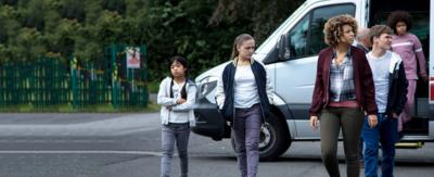 A group of children being dropped off from a minibus into a school grounds.