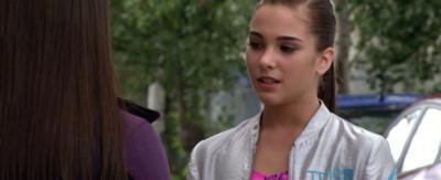 A girl stands outside talking to another girl whilst looking confused, Jacquie from The Next Step.