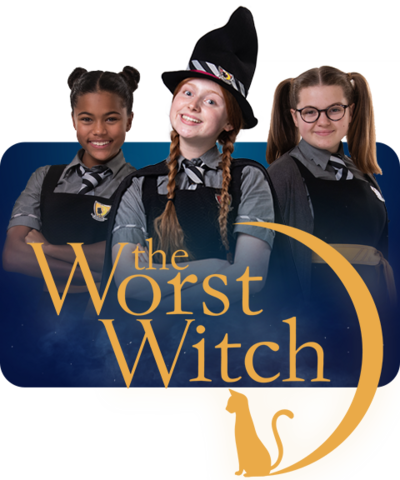 "Three young girls in school uniforms, capes and pointed witch hats all smiling to the camera. Above them is a sign that says ""The Worst Witch"""