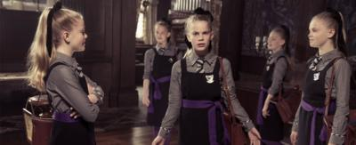 A girl with blonde hair stands in a hall, looking confused as there are copies of herself surrounding her, Ethel from The Worst Witch.