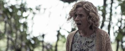 A woman with short blonde curly hair, stands in the woods with a shocked expression.