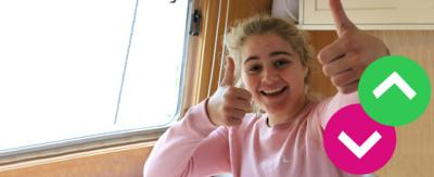 A young girl with both of her hands with thumbs up.