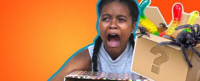 A girl looking scared with her hand in a box. Next to her is a box with gummy worms and toy spiders coming out of it.