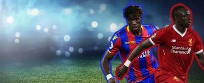 Two football players running in opposite directions. Zaha in a Crystal Palace Kit. Saido Mane in a red Liverpool kit.