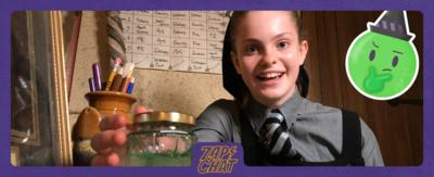 A girl smiling and holding a jar of slime and sat at her desk. Ethel from The Worst Witch.
