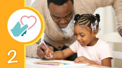Father looking over his daughters shoulder while she colours in a picture
