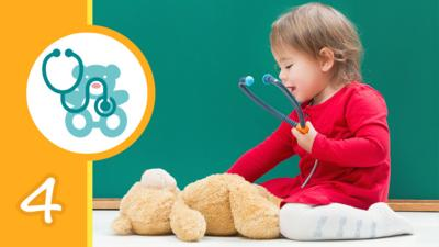 A little girl kneeling over a teddy bear and holding a stethoscope