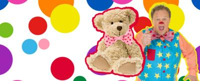 Tumble Ted is sat next to Mr Tumble who is smiling and giving a thumbs up to camera, on a spotted background.