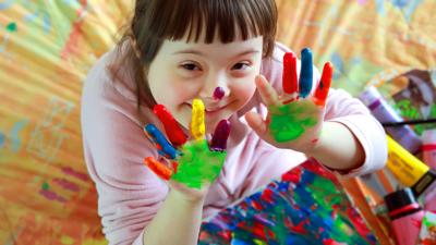Little girl with painted hands smiling