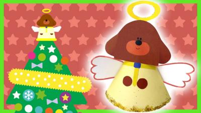 A handmade Duggee angel tree toppers is glowing next to the onscreen version sat on top of a tree.