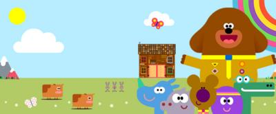Hey Duggee and the squirrels with the hut, animals and a rainbow in the background.
