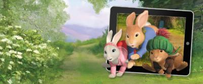 Peter Rabbit, Benjamin Bunny and Lily hopping in front of a tablet device