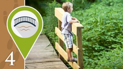A boy stood on a footbridge and looking over the edge