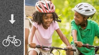 Two children riding biked and they both looks very happy
