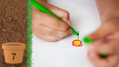 A close up of a childs hands as they colour in a drawing of a flower