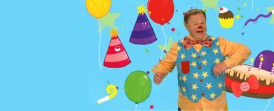 Mr Tumble is mid dance smiling to camera. Behind him is different cartoon party accessories