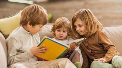 Three siblings reading together