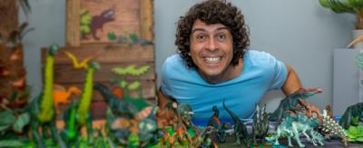 Andy Day behind a table full of toy dinosaurs.