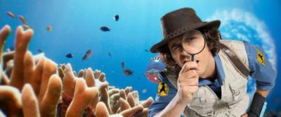 Andy is holding a microscope up to his face with a sea background behind him.