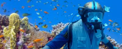 Andy wearing his scuba diving helmet in front of the coral reef surrounded by fish.