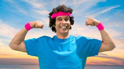Andy Day wearing a blue t-shirt with a pink sweatband on his head and one on each wrist.