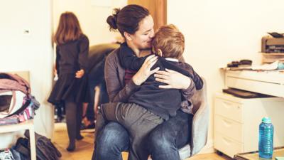 A boy cuddling his mum before school
