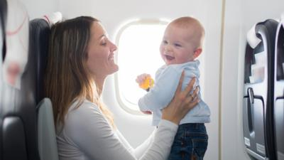 A mother holding her baby in front of her face, smiling, while sat on a plane.