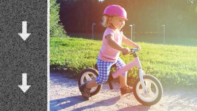 A little girl on her bike pushing herself along with her feet