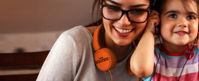 A mother and her daughter listening to sounds through headphones. The mother has orange headphones around her neck with the BBC Sounds logo.