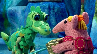 Tiny Clanger from The Clangers handing a golden box to the Soup Dragon.