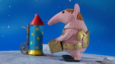 Major Clanger from The Clangers holding a box next to a rocket.