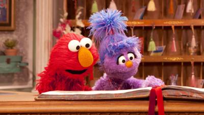 Elmo and Phoebe from The Furchester Hotel behind the reception desk.