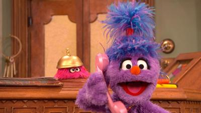 Phoebe from The Furchester Hotel on the phone at the reception desk, with Isabel.