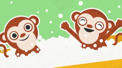 Two monkeys in a bubbly bath.