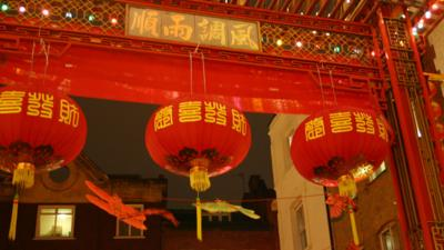 Red paper lanterns underneath a Chinese arch.