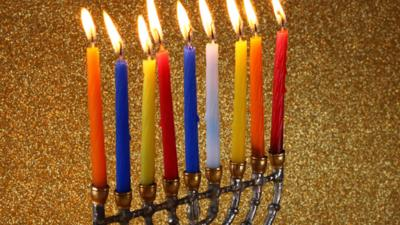 A lit menorah with different coloured candles.