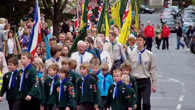A St George's Day scout parade marching down a street.