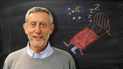 Michael Rosen from Poetry Playtime in front of a blackboard picture of a boy sleeping with one sock on.
